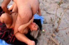 Hitsig oud stel naait op het bloot strand
