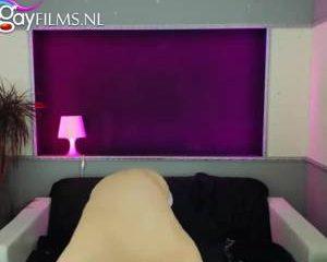 Mooie twink staat glimmend met een stijve lul voor de webcam